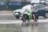 Người đàn ông điều khiển xe môtô, đứng tần ngần giữa trời mưa