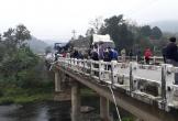 Bánh xe đầu kéo lơ lửng trên mép thành cầu sau cú đâm xe tải