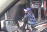 Người phụ nữ ngồi vắt chéo chân, nghe điện thoại khi đang đi xe máy