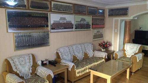 Nhiều bức ảnh khác được trang trí khắp phòng khách, đóng khung cẩn thận, hầu hết là các ảnh tập thể, trong tư thế trang nghiêm.